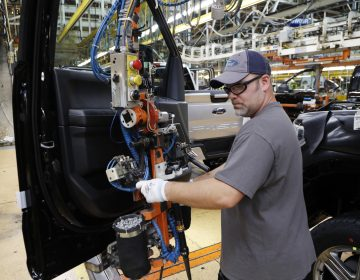 A worker installs a door on a 2018 Ford F-150 truck at an assembly plant in Dearborn, Mich., on Sept. 27. The U.S. unemployment rate fell to 3.7 percent in September, a nearly 50-year low. (Carlos Osorio/AP)