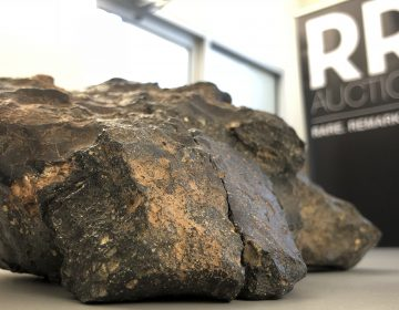 A 12-pound lunar meteorite discovered in Northwest Africa in 2017 rests on a table, in Amherst, N.H. (Rodrique Ngowi/AP)