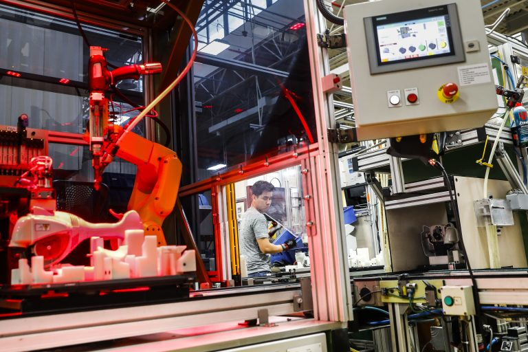In this 2017 photo, an assembly line laborer works alongside a collaborative robot, left, on a chainsaw production line. (AP Photo/John Minchillo)