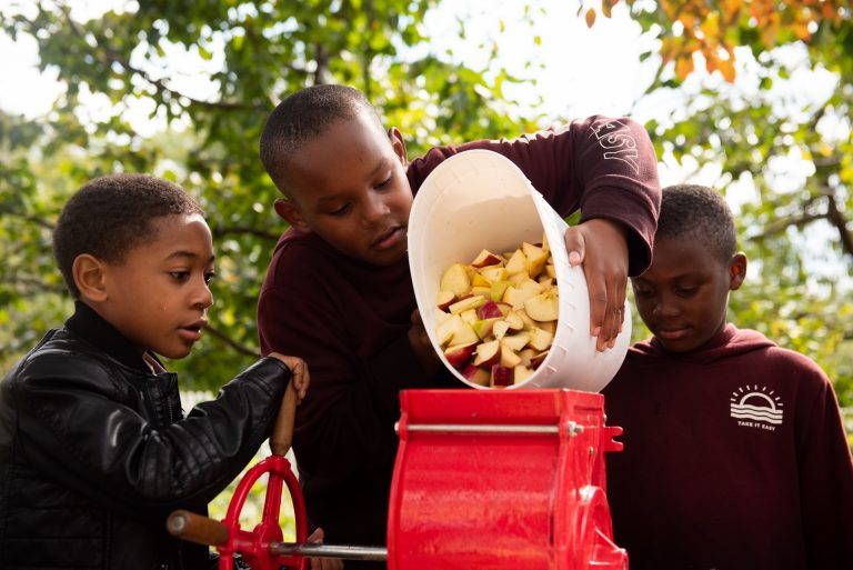 Devin Puckett, along with Clyde and Saheir Beatty, empty a bucket of apples into a fruit grinder during the East Park Apple Festival at Woodford Mansion in Fairmount Park. (Kriston Jae Bethel for WHYY)