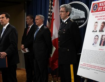 Assistant U.S. Attorney General for National Security John C. Demers, (left), speaks as U.S. Attorney for the Western District of Pennsylvania Scott W. Brady, 3rd from (left), FBI Deputy Assistant Director for Cyber Division Eric Welling, 2nd from (left), and Director General Mark Flynn, (right), for the Royal Canadian Mounted Police listen during a news conference to announce criminal charges Thursday. (Alex Wong/Getty Images)