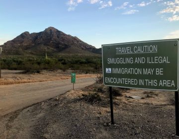 A sign outside Ajo, Ariz., warns hikers to keep an eye out for people who have unlawfully crossed the nearby border with Mexico. (Ryan Lucas/NPR)