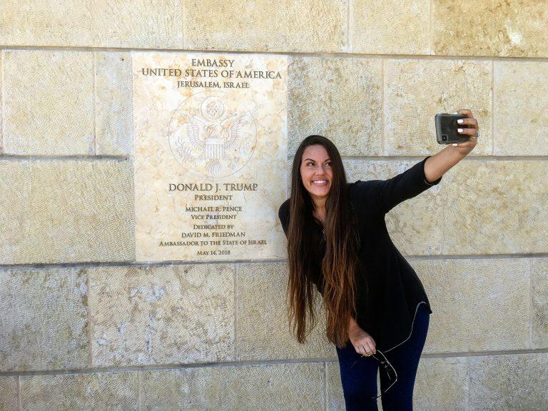 Beckah Shae, a Nashville-based singer-songwriter popular on Christian radio, snapped selfies with the dedication plaque outside the U.S. Embassy to Israel in Jerusalem. (Daniel Estrin/NPR)