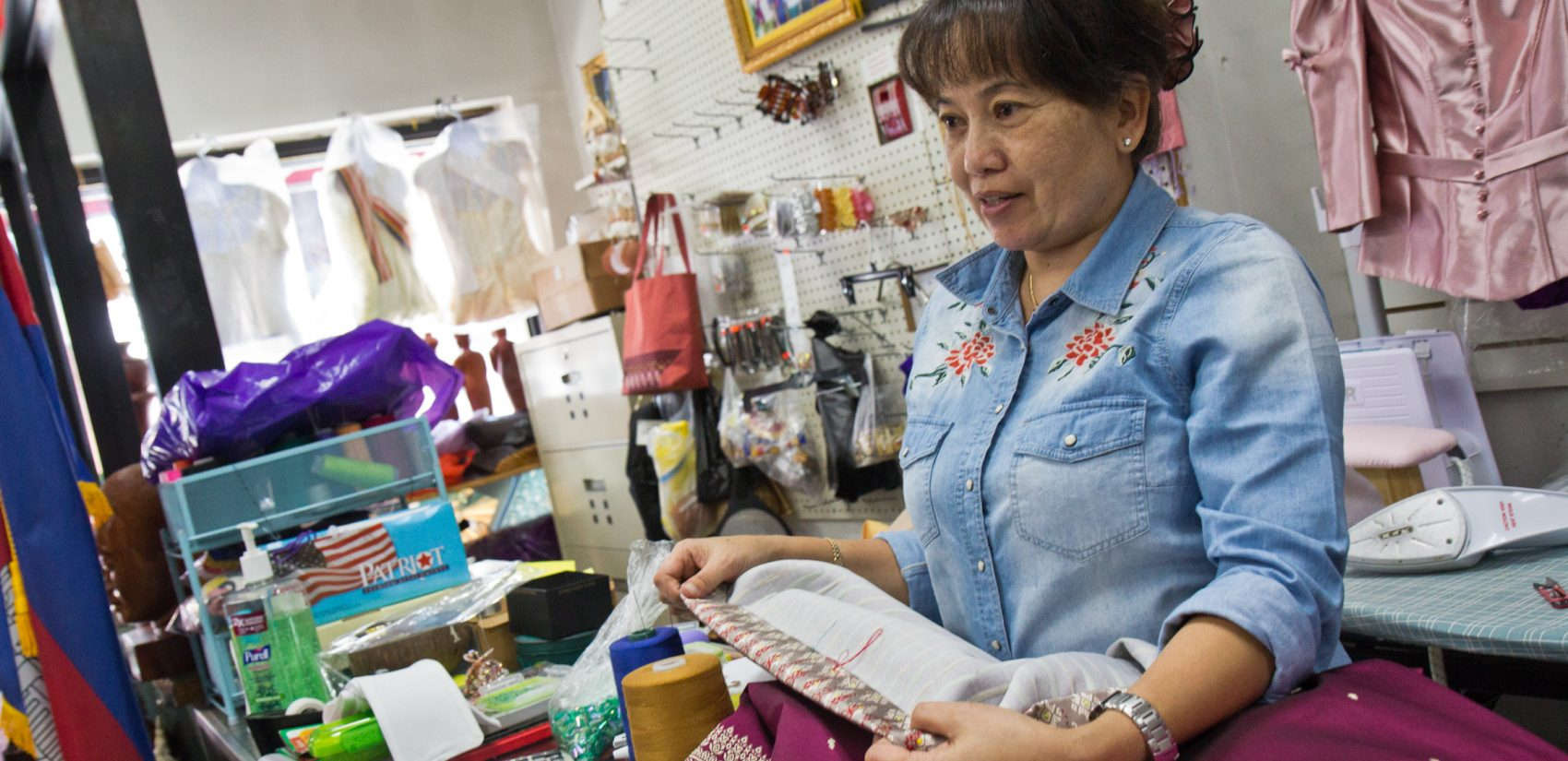 Phally Seng sews in her dress shop on South 7th Street. (Kimberly Paynter/WHYY)