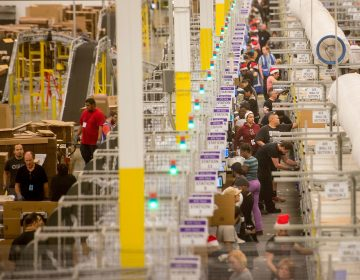 Amazon says it will pay all its U.S. workers at least $15. Here, workers prepare shipments at an Amazon Fulfillment Center in California during the early Christmas rush in2014