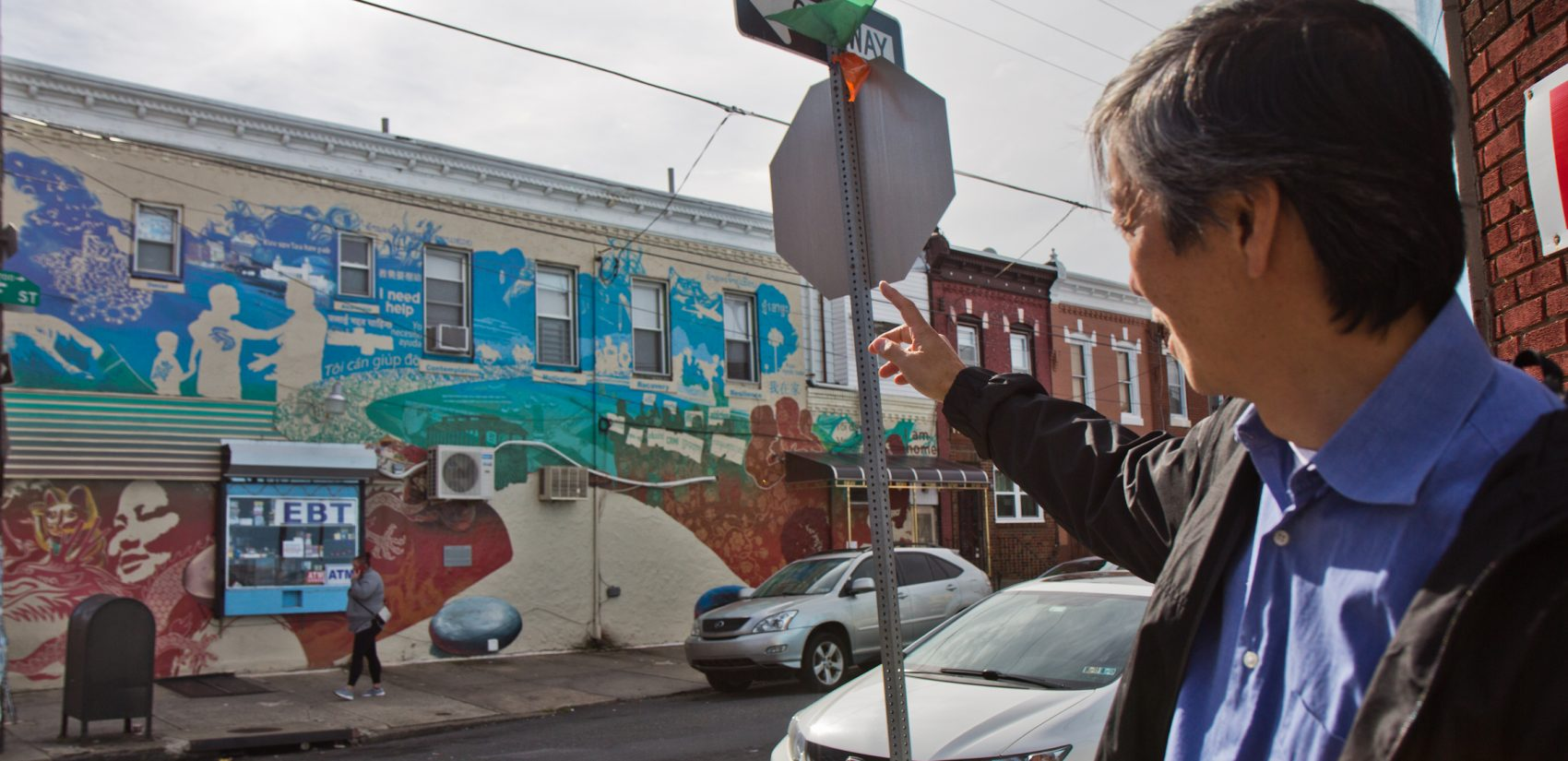 Andy Toy gestures to a mural that created controversy at 7th and Wolf because of it highlighted gambling addiction. (Kimberly Paynter/WHYY)