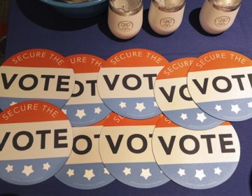 FILE - In this July 14, 2018, file photo, computer mouse pads with Secure the Vote logo on them are seen on a vendor's table at a convention of state secretaries of state in Philadelphia. As alarms blare about Russian interference in U.S. elections, the Trump administration is facing criticism that it has no clear national strategy to protect the country during the upcoming midterms and beyond. Both Republicans and Democrats have criticized the administration's response as fragmented, without enough coordination across federal agencies. (AP Photo/Mel Evans, File)