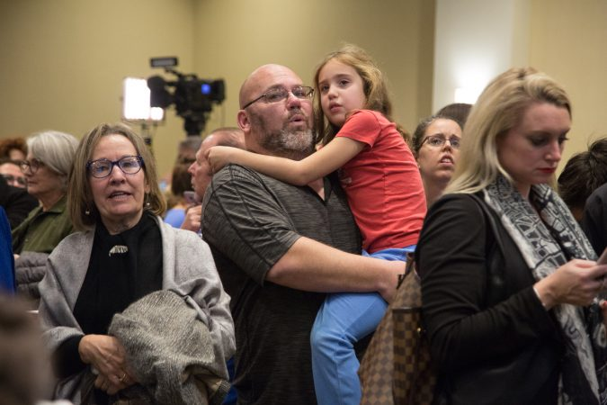 Jason Glass holds his daughter Lexi, 7, as he explains what the numbers on the screens mean in relation to the midterm election. Their family joined the hundreds of supporters who came out to support various Pennsylvania Democratic candidates at the official watch party for Mary Gay Scanlon in Swarthmore, Pa. on November 6, 2018. (Emily Cohen for WHYY)