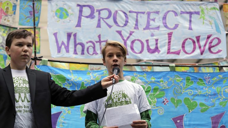Two young people speak at a rally Monday in Seattle. The Supreme Court said it would not stop the lawsuit that inspired this rally, along with others in Portland and Eugene, Ore. (Elaine Thompson/AP)