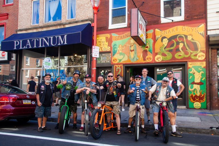 Members of the the Jersey Devils Bicycle Club stood outside of Tattooed Mom's on South Street Sunday. (Brad Larrison for WHYY)