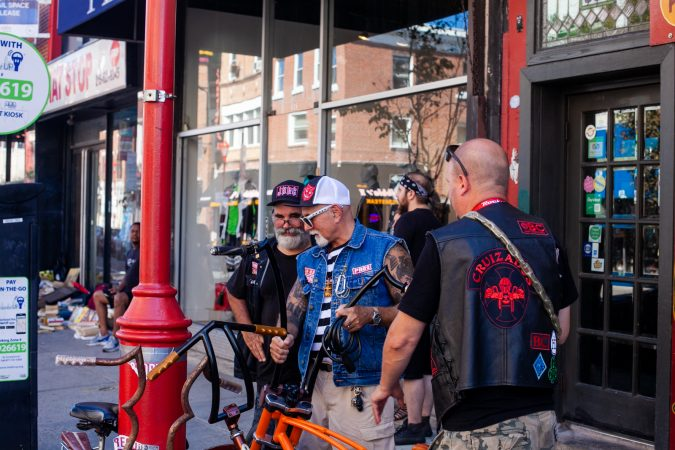 A few riders talk bikes outside of Tattooed Moms. (Brad Larrison for WHYY)