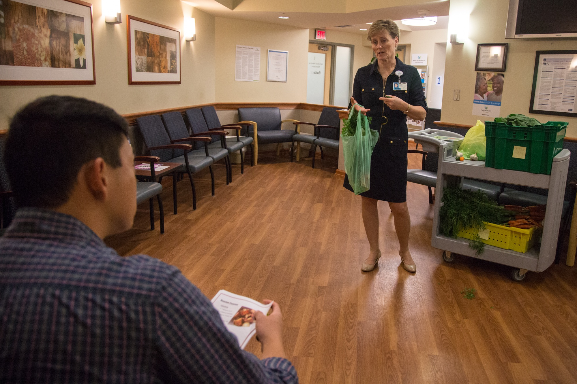 Maureen Krouse talks to Jason Paik about the produce from the hospital's wellness farm, available to him in the waiting room at Lankenau Hospital's integrated health practice.