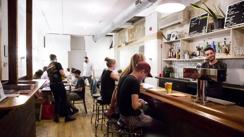 Patrons fill W/N W/N coffee bar on the evening of Oct. 10, 2018. While the bar boasts a wide variety of beverages, the food menu consists solely of pizza by resident chef Daniel Gutter, who cooks under the moniker of Pizza Gutt. (Rachel Wisniewski for WHYY)