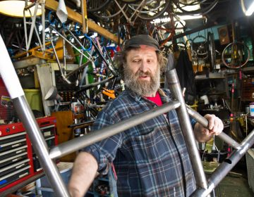 Stephen Bilenky holds a steel bike frame at Bilenky Cycle Works in Philadelphia. (Kimberly Paynter/WHYY)