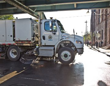 A street sweeper works along Kensington Avenue in Philadelphia. (Kimberly Paynter/WHYY)