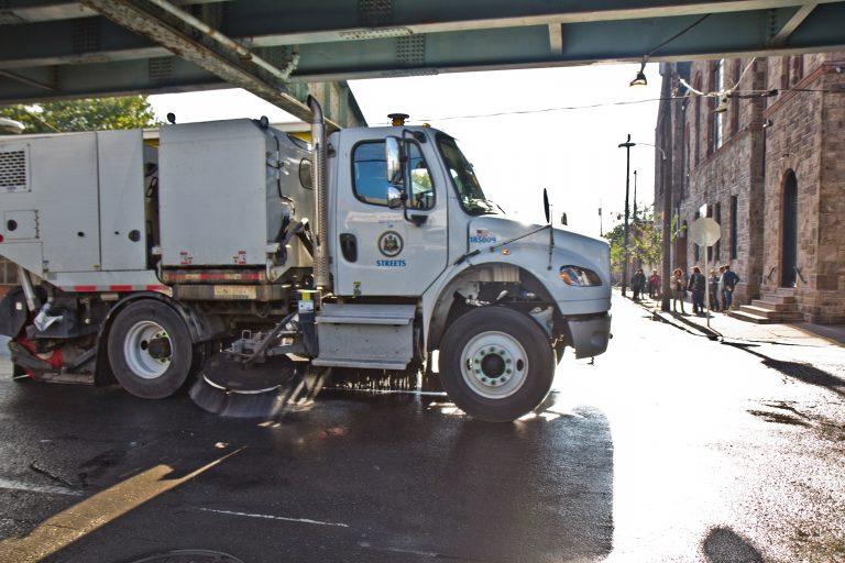 A street sweeper works along Kensington Avenue in Philadelphia. (Kimberly Paynter/WHYY)