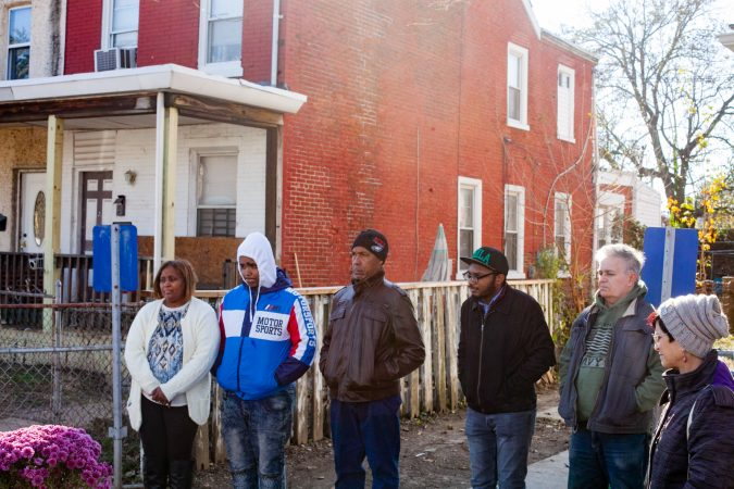 The Mella family, left, stand near their home during a gathering of Tacony residents and neighbors who came out on Saturday to show support for the family who received a threatening and racist letter earlier this month. (Brad Larrison for WHYY)