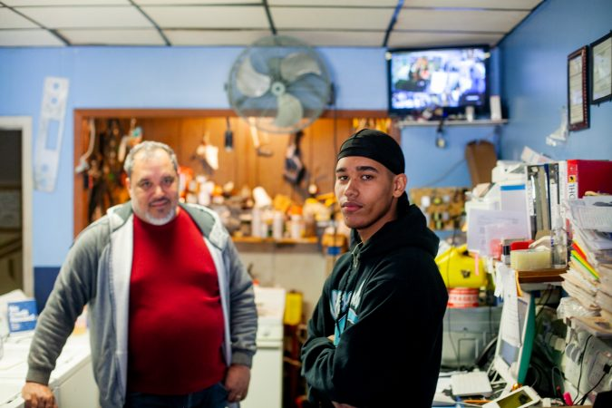 Rolando Rivera, 15, and his father, Javier, inside the Pronto appliance shop, their family business, on Torresdale Avenue in the Tacony section of Philadelphia. (Brad Larrison for WHYY)