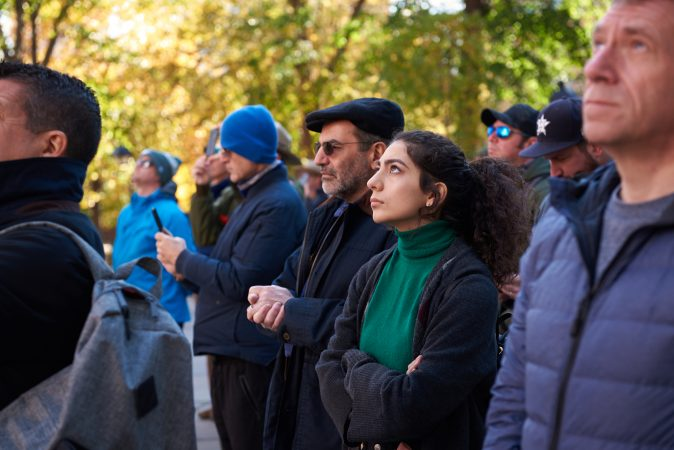 Guita Vahdatina, a resident of California, stands to watch the bell ring at Independence National Historical Park in Philadelphia on the centennial anniversary of Armistice Day on Nov. 11, 2018. (Natalie Piserchio for WHYY)
