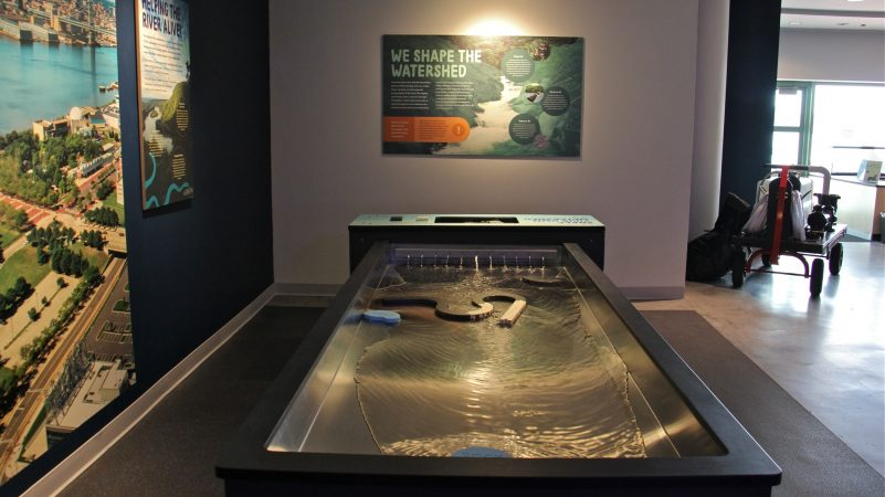 With the watershed modeling table, visitors can interrupt and direct the flow of water, exploring the ways humans alter the course of water for their own uses. (Emma Lee/WHYY)