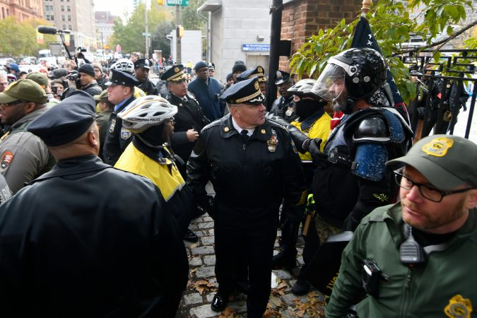 Police officers request Alan Swinney to return to a fenced area after the  protester attempt to interact with counter-protesters on the corner of 5th and Market streets, during the