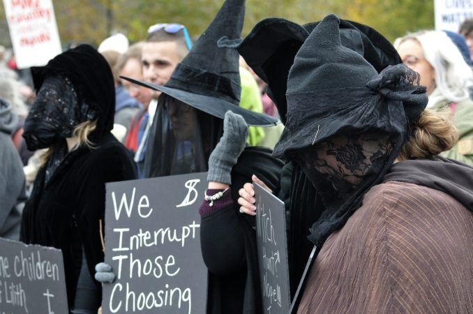 Counter-protesters dressed in witches attire are among a group facing the