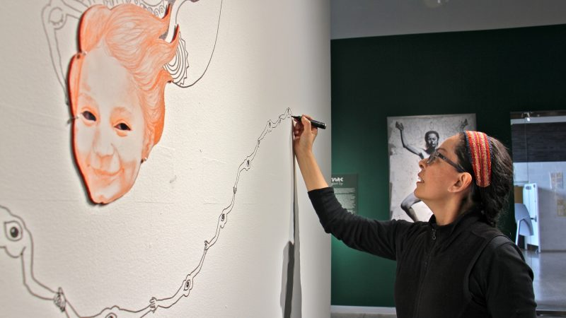 Kukulio Velarde works on a mural that will be completed during the five months that her work is on exhibit at Taller Puertorriqueno. When the exhibit ends, she will repaint the wall white. (Emma Lee/WHYY)