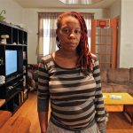 Sherri Lee stands in the living room of her rented home on Snyder Avenue. Plumbing issues there have forced her to seek another home for her family, which includes five children. (Emma Lee/WHYY)