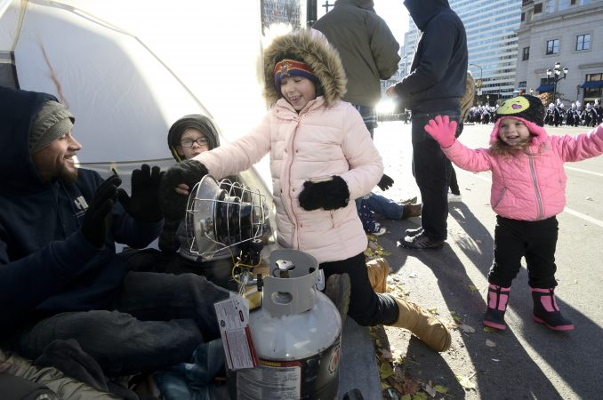 A gas powered heater keeps members of the Gibbons and Eggleston families of Drexel Hill, PA warm as they watch the 99th annual Thanksgiving Day Parade, in Center City Philadelphia. (Bastiaan Slabbers for WHYY)