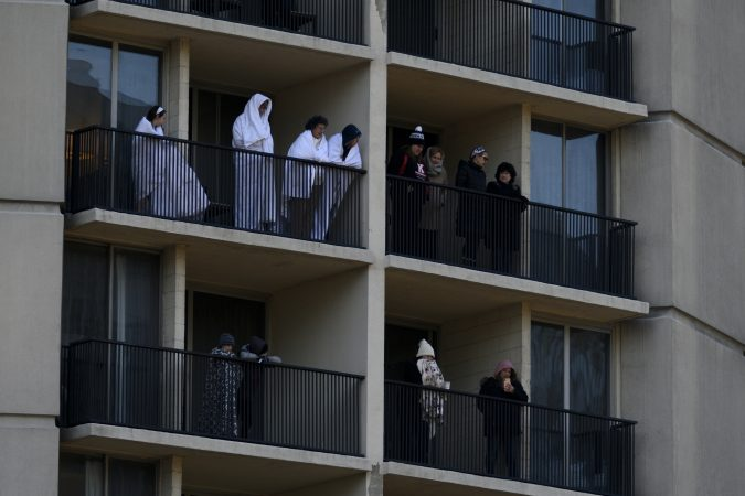 People wrapped in blankets watch from balconies as low temperatures caused a smaller than usual turnout during the 99th annual Thanksgiving Day Parade, in Center City Philadelphia. (Bastiaan Slabbers for WHYY)