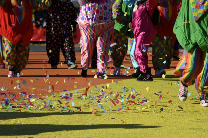 Confetti is picked up by the wind as a group of clowns marches past the cameras at the Art Museum steps, during the 99th annual Thanksgiving Day Parade in Philadelphia. (Bastiaan Slabbers for WHYY)