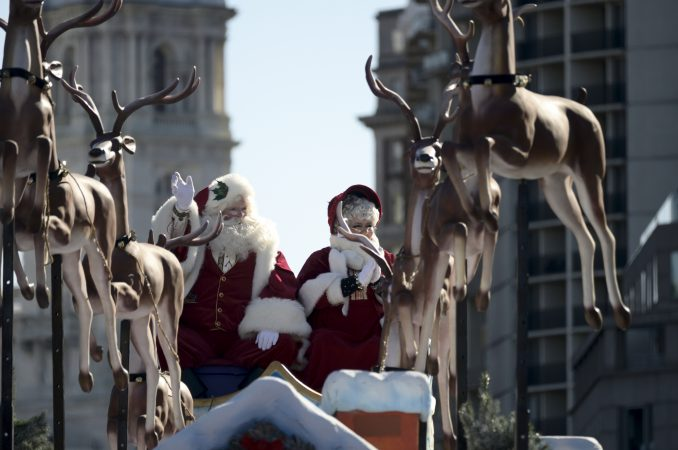 Mr. and Mrs. Claus wave as they close the 99th annual Thanksgiving Day Parade on the Benjamin Franklin Parkway in Philadelphia. (Bastiaan Slabbers for WHYY)