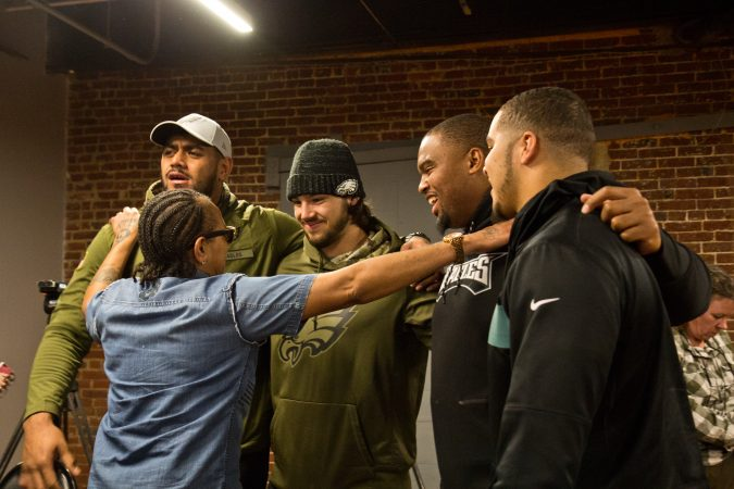 Faith Bartley with the Village of Arts and Humanities in Philadelphia meets members of the Philadelphia Eagles football team. (Kimberly Paynter/WHYY)