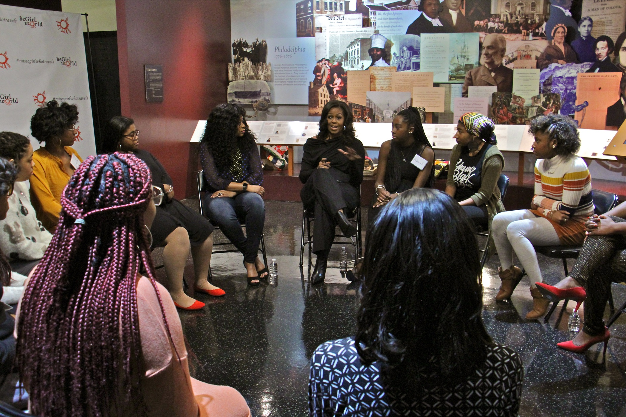 A dozen teens involved in the beGirl.world program, a Philadelphia non-profit that encourages travel and global education for girls, meet with former first lady Michelle Obama at the African American Museum in Philadelphia.