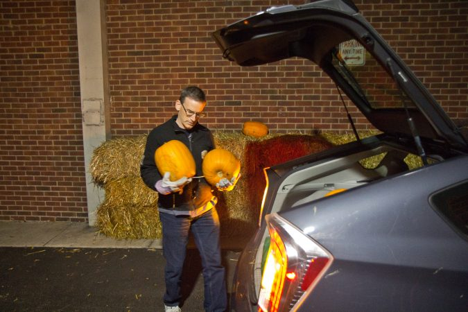 Steve Levy loads pumpkins into his car as during a collection in South Philadelphia. (Kimberly Paynter/WHYY)