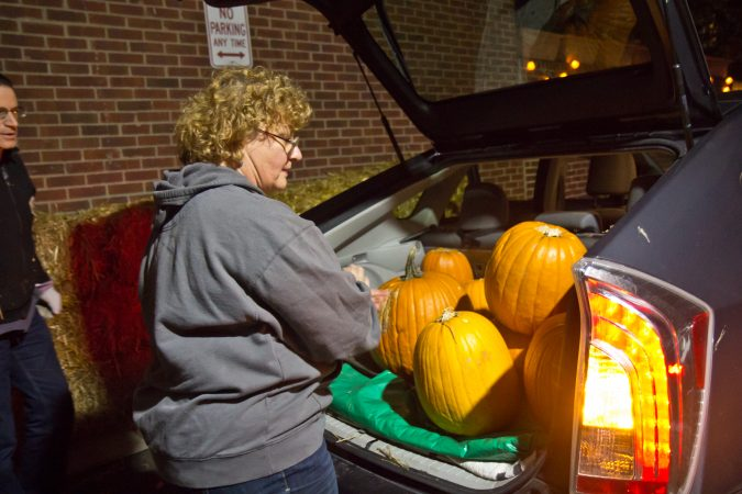 Steve Levy and Lucia Kubik load pumpkins into their car during a donation pickup around South Philadelphia. (Kimberly Paynter/WHYY)