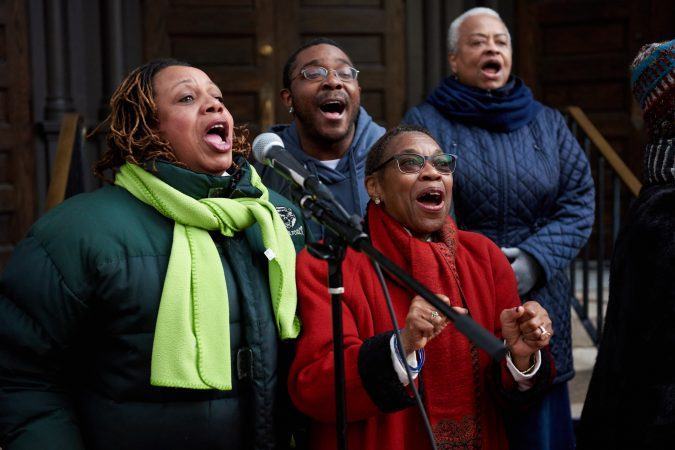 The Mother Bethel A.M.E. Church Choir lines up outside the church on the morning of Sunday, Nov. 18, 2018, and sings as participants of the Philadelphia Marathon run past. Some members include (from left) Beverly Renfrow, Michael Wyche, and Winnefred Rowell-Bullard. (Natalie Piserchio for WHYY)