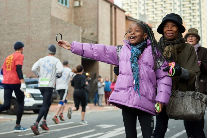 Brehana Mejia, 9, a young member of Mother Bethel A.M.E. Church, stands with Yvonne Hylton, and hands wristbands out to participants of the Philadelphia Marathon as they run past the church on Sunday, Nov. 18, 2018. She says her favorite part of the church is the singing. (Natalie Piserchio for WHYY)