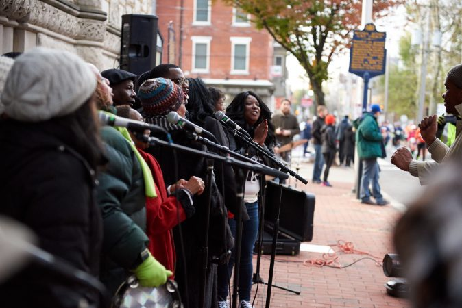 The Mother Bethel A.M.E. Church Choir lines up outside the church on the morning of Sunday, Nov. 18, 2018, and sings as participants of the Philadelphia Marathon run past. (Natalie Piserchio for WHYY)