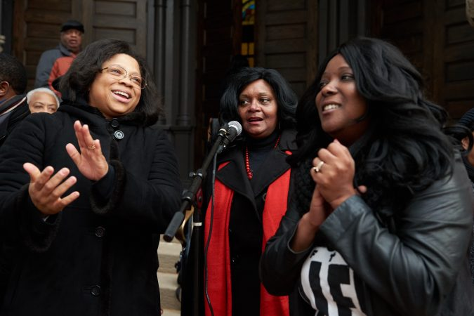 (From left) Joetta Cryer, Gloria Johnson, and Selah Wyche share a microphone and sing on the front steps of Mother Bethel A.M.E. Church on Sunday, Nov. 18, 2018. They are part of the mass choir who sang and cheered while thousands of participants in the 2018 Philadelphia Marathon ran past them on Sixth street. (Natalie Piserchio for WHYY)