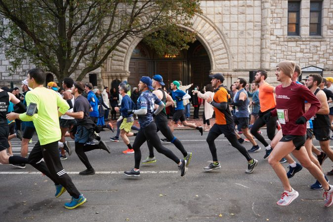 Participants of the 2018 Philadelphia Marathon run past Mother Bethel A.M.E. Church while members of the church sing on the front steps. (Natalie Piserchio for WHYY)