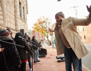 Jonas Crenshaw, Jr. conducts the Mother Bethel A.M.E. Mass Choir outside the church, as participants of the 2018 Philadelphia Marathon run up Sixth Street, along their route. (Natalie Piserchio for WHYY)