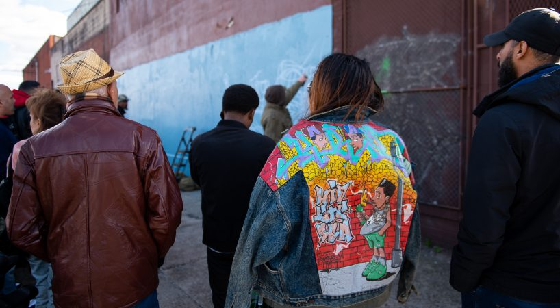 Ashley Sanchez, niece to the late graffiti writer Karaz, wears his jacket while a mural is painted in his honor in Hunting Park on Saturday, November 3, 2018. During large gatherings, like this send off, writers often bring books that they have others sign. (Kriston Jae Bethel for WHYY)