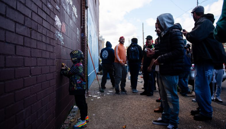 Silas, age 5, adds his own art to a wall tagged by other writers during a memorial and mural paiting dedicated to Karaz on Saturday, November 3, 2018. (Kriston Jae Bethel for WHYY)