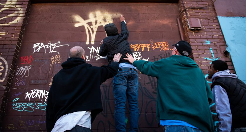 Graffiti writers tag a wall adjacent to a mural dedicated to the late graffiti writer Karaz on Saturday, November 3, 2018. (Kriston Jae Bethel for WHYY)