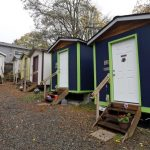 In this 2017 photo, a resident walks past a row of tiny houses at a homeless encampment in Seattle. (Elaine Thompson/AP Photo, file)