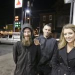 In this Nov. 17, 2017, file photo, Johnny Bobbitt Jr., (left), Kate McClure, (right), and McClure's boyfriend Mark D'Amico pose at a Citgo station in Philadelphia.  McClure and D'Amico, who raised more than $400,000 for Bobbitt Jr., a homeless man after he used his last $20 to fill up the gas tank of a stranded motorist in Philadelphia must now turn over what's left of the cash. A New Jersey judge issued the order Thursday, Aug. 30,  during a hearing on the lawsuit brought by Bobbitt, who worries D'Amico and McClure have mismanaged a large part of the donations raised for him on GoFundMe. The couple deny those claims, saying they're wary of giving Bobbitt large sums because they fear he would buy drugs. (Elizabeth Robertson/The Philadelphia Inquirer via AP)