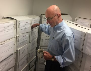 In this Aug. 7, 2018, photo, Mark Robbins, the sole member of the Merit Systems Protection Board, walks through the supply closet, pointing to boxes full of cases, in his office in Washington. Robbins reads through federal workplace disputes, analyzes the cases, marks them with notes and logs his legal opinions. He then passes them along to nobody. He's the only member of a three-member board that legally can't operate until the president and Congress give him at least one colleague.  (Juliet Linderman/AP Photo)