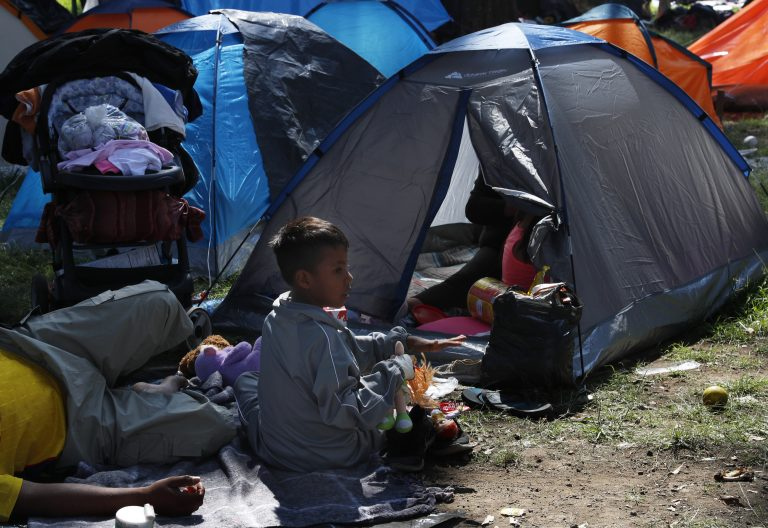 A migrant child sits outside a tent, taking shelter at the Jesus Martinez stadium in Mexico City, Tuesday, Nov. 6, 2018. Humanitarian aid converged around the stadium in Mexico City where thousands of Central American migrants winding their way toward the United States were resting Tuesday after an arduous trek that has taken them through three countries in three weeks. (Marco Ugarte/AP Photo)
