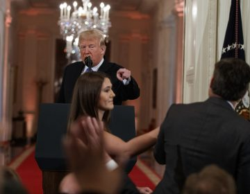 President Donald Trump looks on as a White House aide attempts to take away a microphone from CNN journalist Jim Acosta during a news conference in the East Room of the White House, Wednesday, Nov. 7, 2018, in Washington. (Evan Vucci/AP Photo)